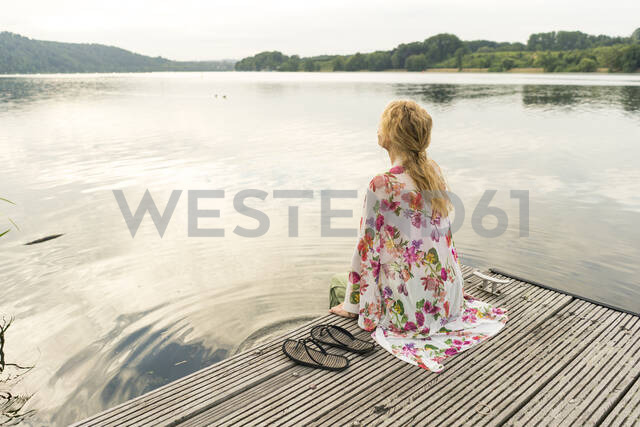 Young woman sitting on a jetty at a lake - JOSF03623 - Joseffson/Westend61