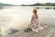 Young woman sitting on a jetty at a lake - JOSF03623