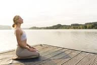 Young woman practicing yoga on a jetty at a lake - JOSF03632