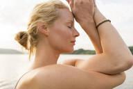 Close-up of young woman with closed eyes at a lake - JOSF03635