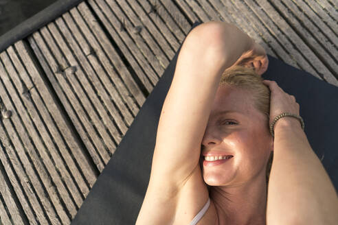 Top view of smiling young woman lying on a jetty - JOSF03638