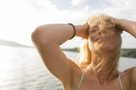 Young woman with windswept hair at a lake - JOSF03641