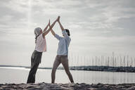 Mother and daughter spending a day at the sea, high-fiving - JOSF03654