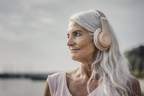 Senior woman listening music with headphones at the sea, poartrait - JOSF03663