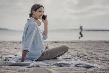 Woman sitting on the beach, talking on the phone - JOSF03684