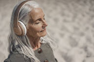Senior woman listening music with headphones on the beach - JOSF03690