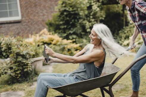 Senior woman sitting push cart, using digital tablet - JOSF03726
