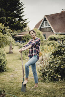 Proud home owner standing in her garden with a spade - JOSF03729