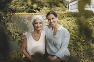 Mother and dahughter enjoying time together, sitting a garden - JOSF03744