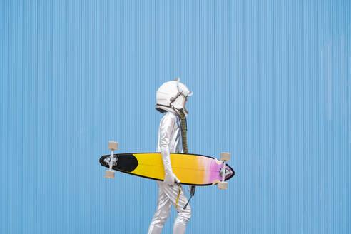 Kid dressed as an astronaut with longboard - DAMF00037