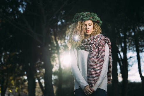 Portrait of young woman with Christmas wreath on her head in nature - DAMF00052