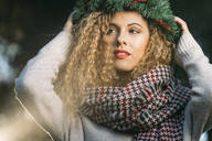 Portrait of young woman wearing Christmas wreath on her head - DAMF00055