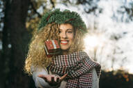 Portrait of smiling young woman with Christmas wreath on her head juggling with Christmas present - DAMF00058