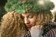Portrait of smiling young woman wearing Christmas wreath on her head - DAMF00061