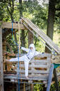 young, cool boy dressed as a superhero astronaut playing in a beautiful, tree house in the afternoon sun, lower austria, austria - HMEF00540