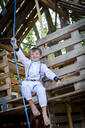 young, cool boy dressed as a superhero astronaut playing in a beautiful, tree house in the afternoon sun, lower austria, austria - HMEF00543