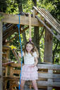 Girl dressed as a princess with crown and sceptre playing in a tree house - HMEF00552