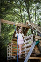 Girl dressed as a princess with crown and sceptre playing in a tree house - HMEF00555