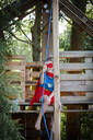 Superhero girl playing in a tree house - HMEF00564