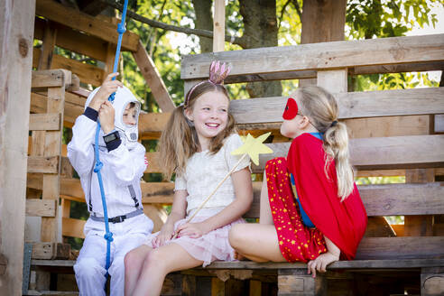 Three kids with superheroes costumes playing on their tree house - HMEF00567