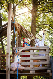 Three kids with superheroes costumes playing on their tree house - HMEF00570