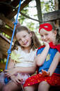 Girls dressed up as princess and superwoman playing in a tree house - HMEF00576