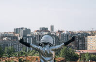 Rear view of boy dressed with raised arms as an astronaut in the city - JCMF00209