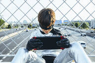 Boy disguised as superhero using games cosole above the streets of the city - JCMF00212
