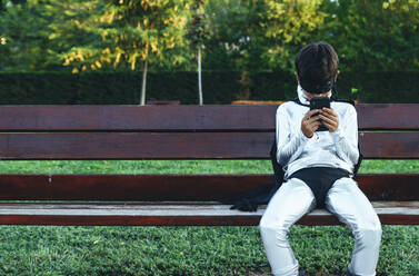 Portrait of boy disguised as superhero using mobile phone on park bench - JCMF00215