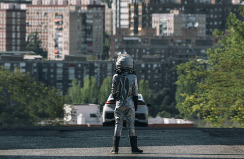 Rear view of boy dressed as an astronaut standing on a street in the city - JCMF00218