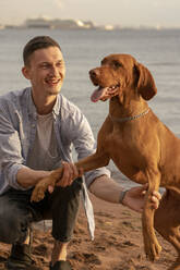 Young man with his dog at the beach, dog giving paw - VPIF01526