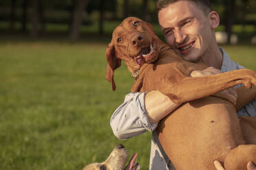 Young man with his dog, cuddling on a meadow - VPIF01529