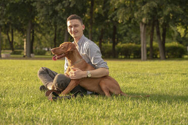 young man with his dog on a meadow - VPIF01532