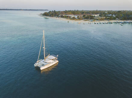 Drone shot of catamaran on sea at Gili-Air Island against clear sky during sunset, Bali, Indonesia - KNTF03443