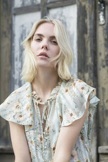 Portrait of blond young woman wearing summer blouse with floral design - JESF00318