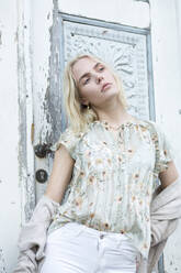 Portrait of blond young woman wearing summer blouse with floral design - JESF00321