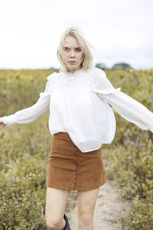 Portrait of blond young woman wearing white blouse dancing on sunflower field - JESF00327