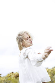 Portrait of blond young woman wearing white blouse dancing on sunflower field - JESF00330