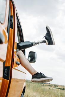 Legs of prosthetic young man dangling out of camper van window - CJMF00012