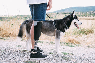 Young man wearing leg prosthesis with dog on dirt track - CJMF00015