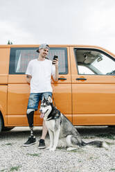 Young man with dog wearing leg prosthesis and using cell phone at camper van - CJMF00018