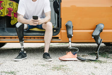 Young man with leg prosthesis sitting in camper van using cell phone - CJMF00021