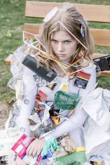 Junges Mädchen in weissem Kleid, mit Müll bedeckt vor einer Bank, Vilsbiburg, Bayern, Deutschland - STBF00388