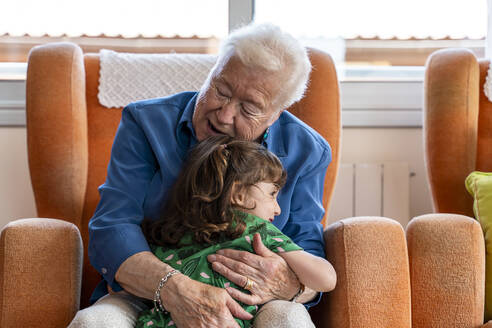 Grandmother hugging her granddaughter in living room - GEMF03153