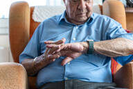 Elderly man wearing a smart emergency alarm bracelet around wrist at home - GEMF03159