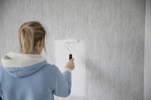 Back view of woman painting wall - CHPF00579