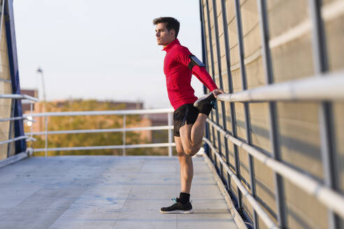 Jogger with smartphone in arm pocket, stretching his leg on a bridge railing - JSRF00584