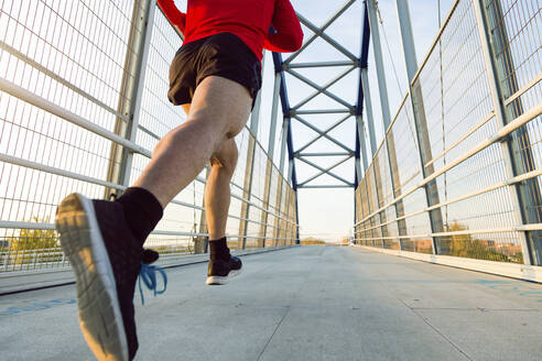 Jogger with smartphone in arm pocket running on a bridge - JSRF00587