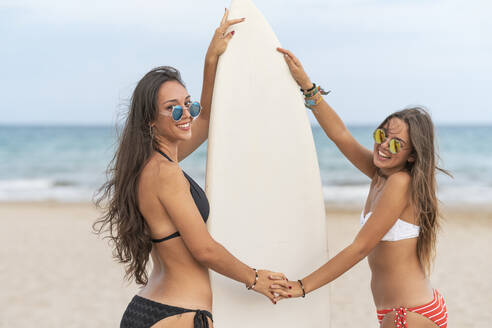 Two happy female friends hand in hand on the beach with surfboard - DLTSF00131
