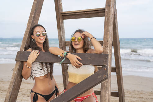 Portrait of two happy female friends at a wooden ladder on the beach - DLTSF00140